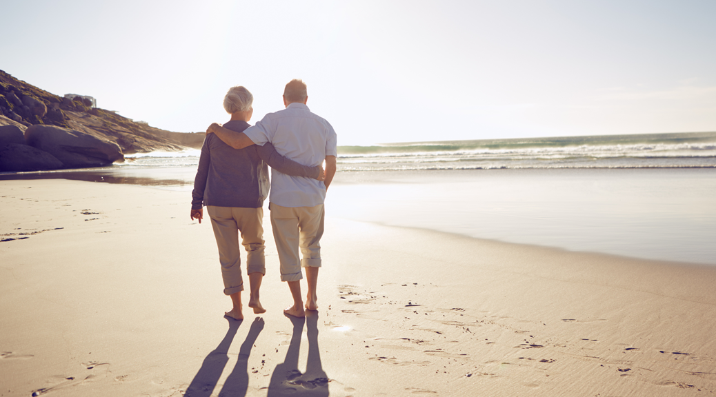 Couple walking closely on beach