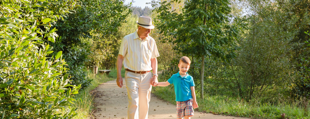 Front view of grandfather with hat and grandchild walking on a nature path ** Note: Shallow depth of field