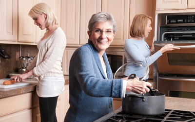 Older woman cooking with daughter