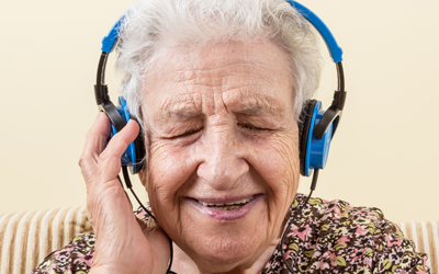 Older woman listening to music through headphones