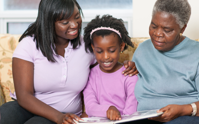 Older woman looking at photo album with daughter and granddaughter